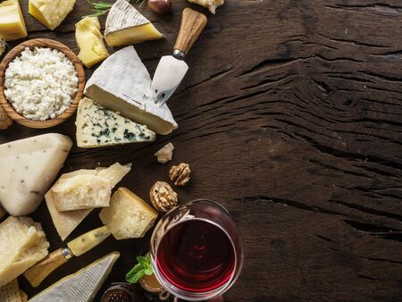 Cheeses with organic cheeses, fruits, nuts and wine on old wooden