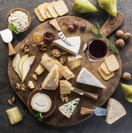Cheese platter with different cheeses, fruits, nuts and wine on stone