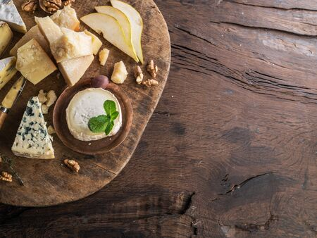 Cheese platter with organic cheeses, fruits, nuts on wooden table. Top view.