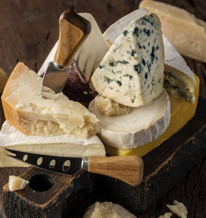 Assortment of different cheese types on wooden background. Cheese background. 写真素材