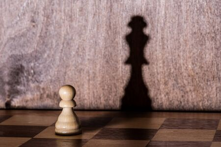Chess pawn with queen shadow on chess-board. Conceptual picture - dreaming and confidence in one's strength.