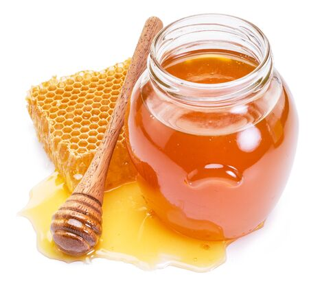 Vaso pieno di miele fresco e favi isolati su sfondo bianco.