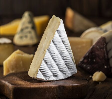 Segment of  Brie cheese or soft cows - milk  French cheese on wooden board. Different cheeses at the background.