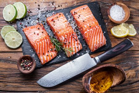 Fresh salmon fillets on black cutting board with herbs and spices. Top view.