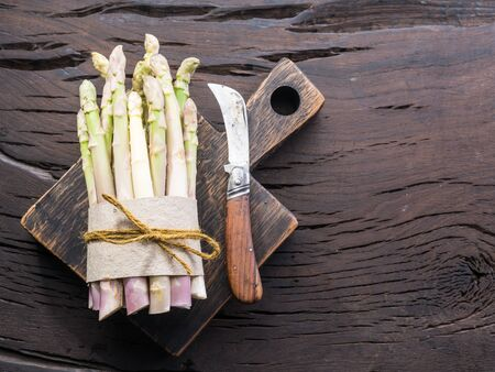 White fresh asparagus sprouts on wooden table. Royal vegetable. Top view.
