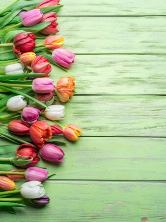 Colorful  bouquet of tulips on green wooden background. Top view.