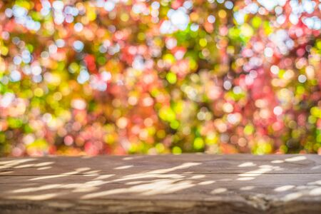 Autumn background with a wooden table and beautiful sunny bokeh.