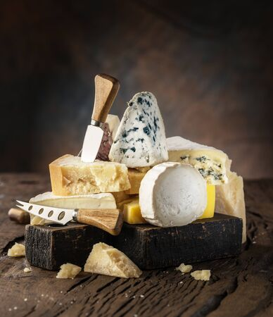 Assortment of different cheese types on wooden background. Cheese background. Banco de Imagens