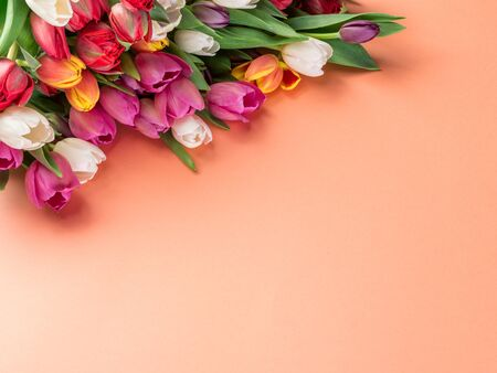 Colorful  bouquet of tulips on orange background.  Top view.