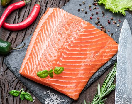 Fresh salmon fillet on black cutting board with herbs and spices. Top view. Banco de Imagens