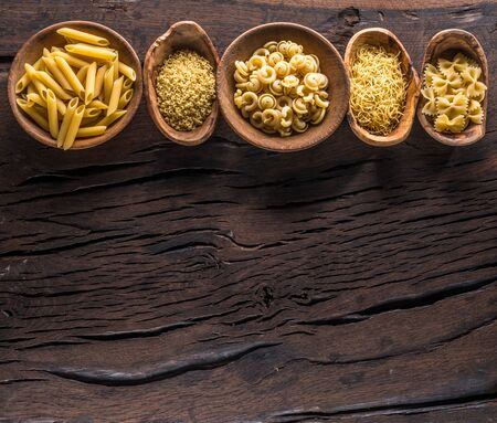 Different pasta types in wooden bowls on the table. Top view. Banco de Imagens