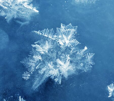 Snowflakes as a snow butterflies over frozen icy river. Frosty nature background. Banco de Imagens