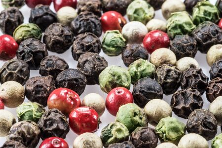 Black, white, green and red peppercorns isolated on white background. Banco de Imagens