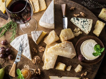Cheese platter with organic cheeses, fruits, nuts and wine on wooden background. Top view. Tasty cheese starter. Standard-Bild