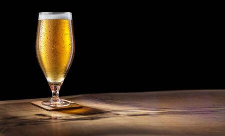 Glass of light beer on the bar counter on a black background. Clipping path.