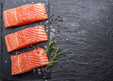 Fresh salmon fillets on black cutting board with herbs and spices. Banco de Imagens