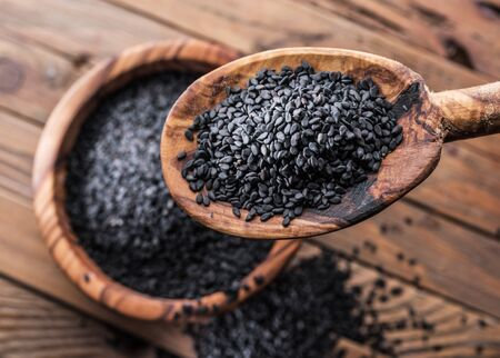 Black sesame seeds in the wooden spoon. Old wooden table and dish at the background. Top view. Banco de Imagens