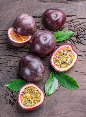 Passion fruits and its cross section with pulpy juice filled with seeds. Wooden background. Banco de Imagens
