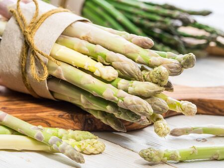 Bundles of green and white asparagus on wooden board. Organic food. Close-up.