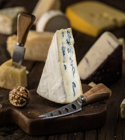 Segment of blue cheese or Cambozola cheese on wooden board. Different cheeses at the background. Banco de Imagens