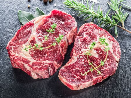 Raw Ribeye steaks or beef steak on graphite tray with herbs.