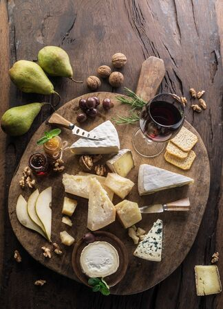 Cheese platter with organic cheeses, fruits, nuts and wine on wooden background. Top view. Tasty cheese starter. 写真素材