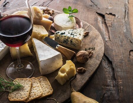 Cheese platter with organic cheeses, fruits, nuts and wine on wooden background. Tasty cheese starter.