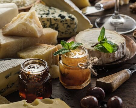 Cheese platter with organic cheeses, fruits, olives and jam on wooden background. Tasty cheese starter.