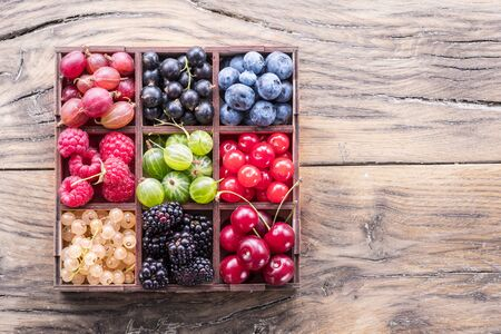 Colorful berries in wooden box on the table. Top view. Stock Photo