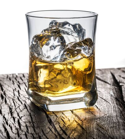 Whiskey glass or glass of whiskey with ice cubes on the table at white background.