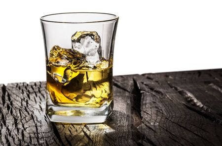 Whiskey glass or glass of whiskey with ice cubes on table at the white background.