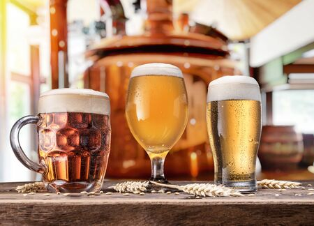Beer glasses on wooden table and copper brewing cask at the background. Craft brewery.