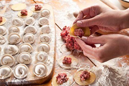 Dumplings. Dough with meat filling on the cooks hands. Banco de Imagens
