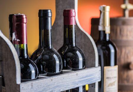 Botellas de vino en caja de madera y barril de roble.