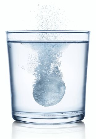 Effervescent tablet dissolving in a glass of water. Isolated on white background.