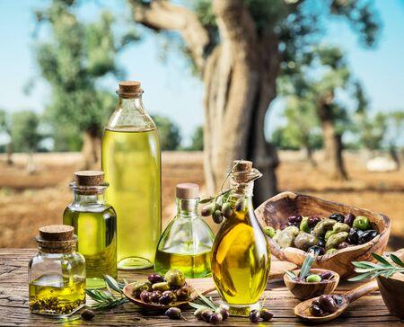 Olijfolie en bessen staan op de houten tafel onder de olijfboom. Stockfoto