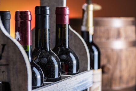 Wine bottles in wooden crate and oak wine keg. 免版税图像
