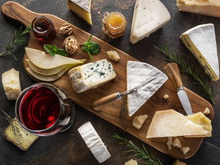 Cheese platter with different cheeses, fruits, nuts and wine on stone background. Top view. Tasty cheese starter. Stok Fotoğraf
