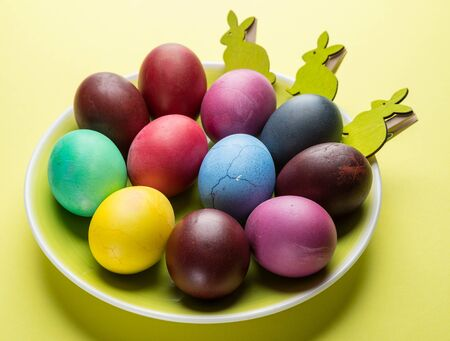 Colorful Easter eggs as an attribute of Easter celebration on the yellow plate.