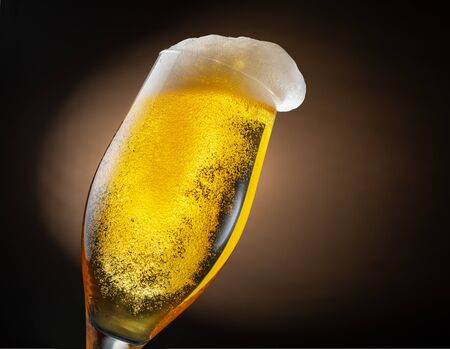 Glass of beer on a dark brown background. Inside the beer glass there are a lot of bubbles and foam.