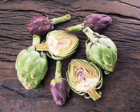 Green and purple artichoke flower edible buds on wooden background.