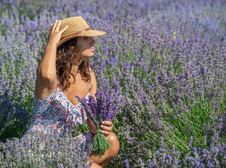 Woman in straw hat with lavender bouquet in the lavender field. Archivio Fotografico
