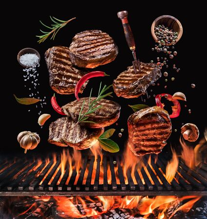 Grilled beef steaks and vegetables in motion falling down on open grill.  Conceptual photo of meat or barbeque cooking process.