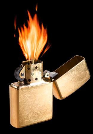 Burning golden metal gas lighter on black background.