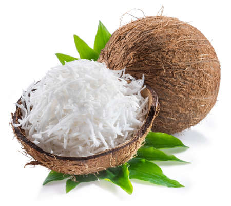 Cracked coconut fruit with white shredded flesh and whole coconut isolated on white background. Archivio Fotografico