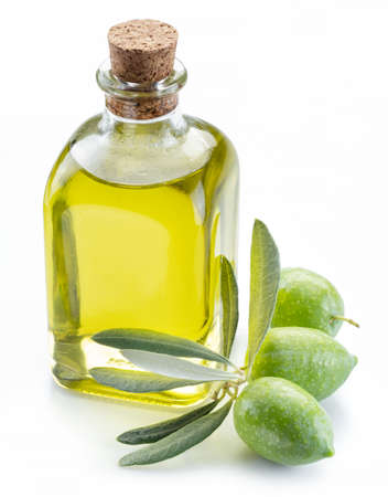 Green natural olives with bottle of olive oil isolated on a white background. Фото со стока