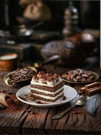 Slice of chocolate cake with tiramisu cream and cocoa powder on wooden table.