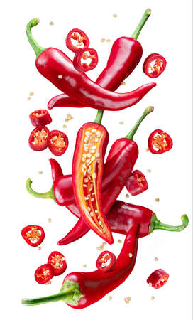 Fresh red chili peppers and cross sections of chili pepper with seeds floating in the air. Фото со стока