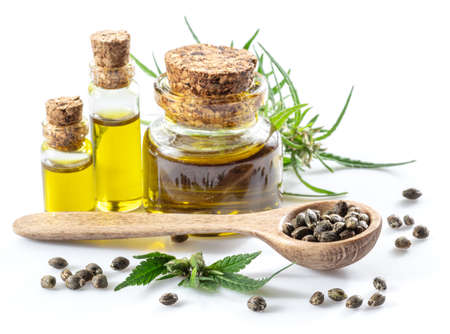 Cannabis seeds in the wooden spoon and bottles of hemp oil is