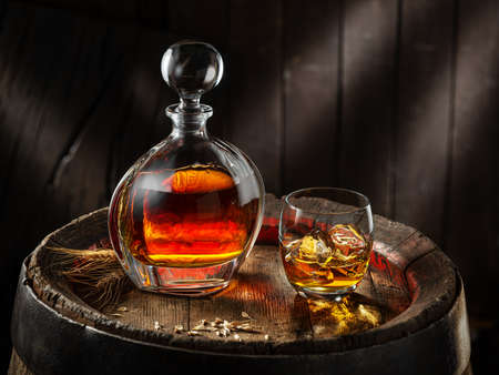 Carafe of whiskey and glass of whiskey on old wooden cask